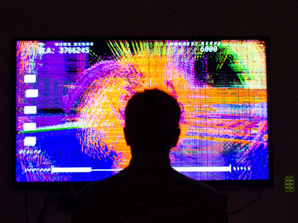 Player stands in front of glitch art game.