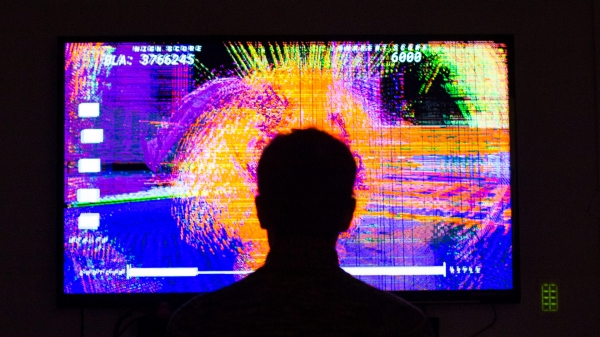 Player in front of neon game screen.