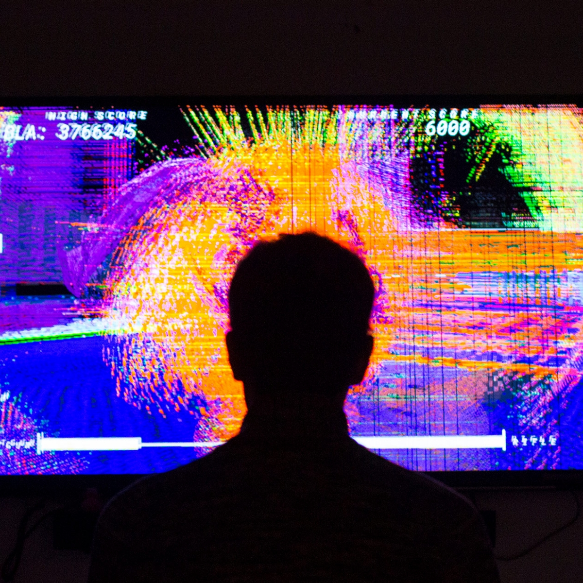 Person stands in front of vibrant screen.