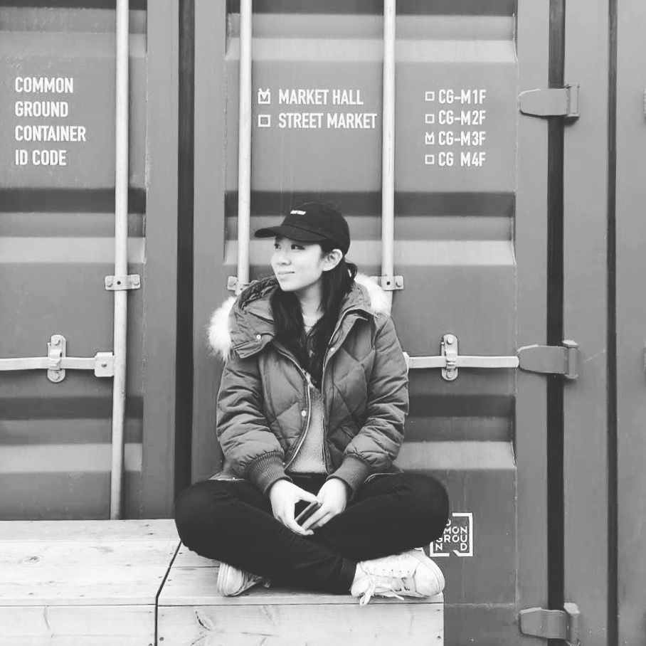 woman sitting in front of shipping container