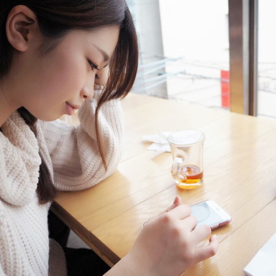 Haruka Shibata sits at a table and uses the phone with her finger