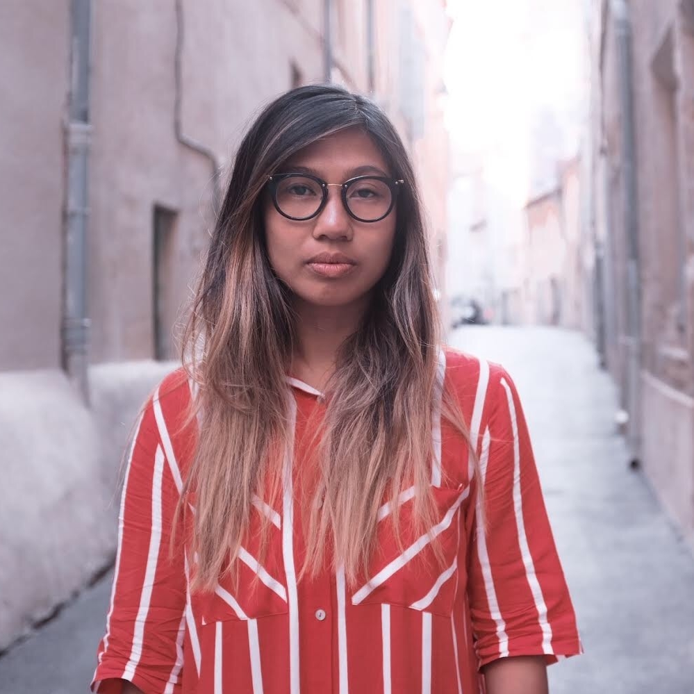 Kristel standing in a narrow stone street wearing a red and white striped shirt.