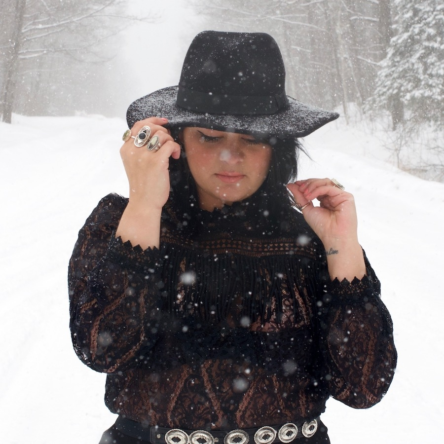 Tashina Emery wears black jacket and hat in a snowfall. She is looking down with one hand on her hat