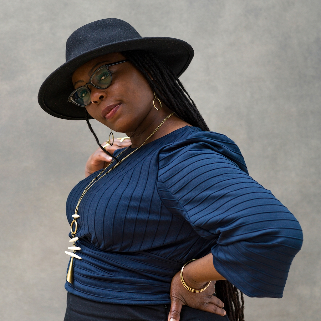 Black woman wears blue long sleeve top and black hat and glasses and poses facing left with hand on hip and head tilted toward camera