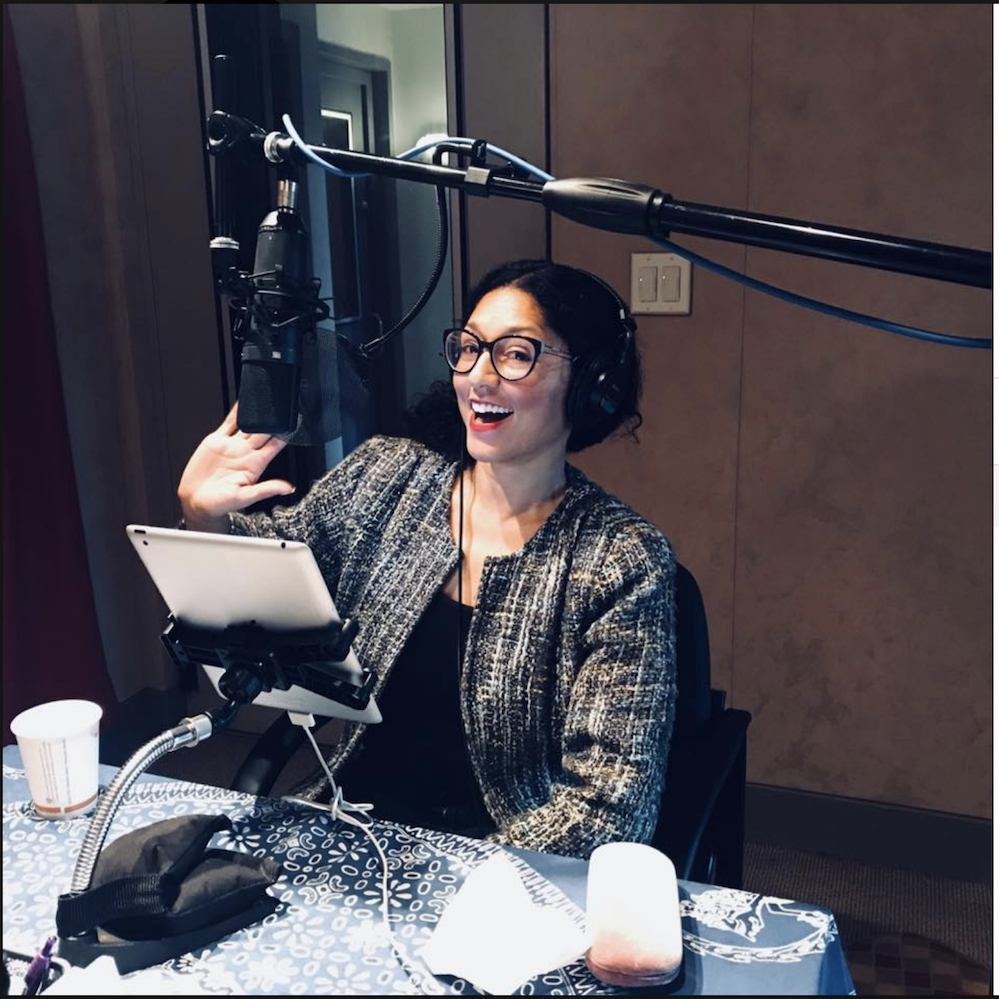 Maya Contreras in glasses sits at a mic in a recording studio