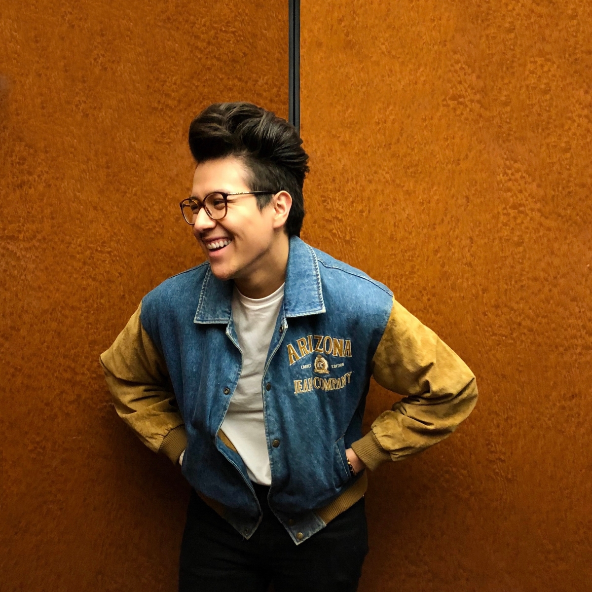 Antonio wears glasses and a denim jacket with suede sleeves, smiling away from the camera.