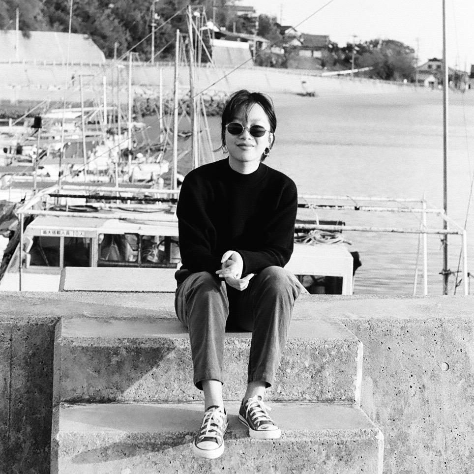 Sydney Tang wears sunglasses and sits on a dock by the water.