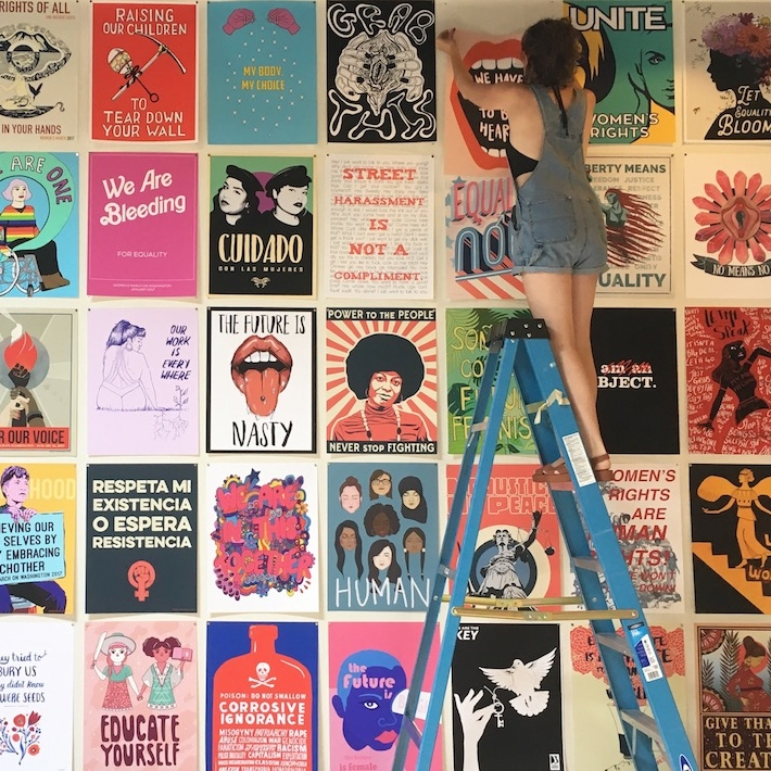 Cleo Barnett on a ladder in front of colorful posters