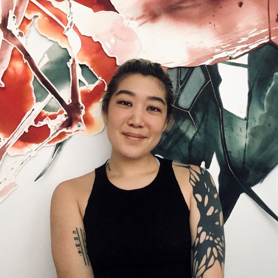 GB Kim in black tank top in front of abstract mural