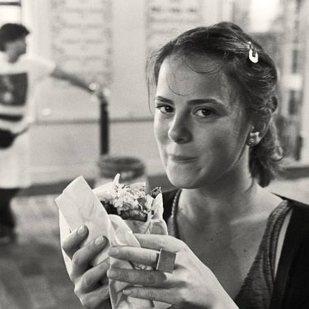 Black and white Mariana Acevedo holding a sandwich