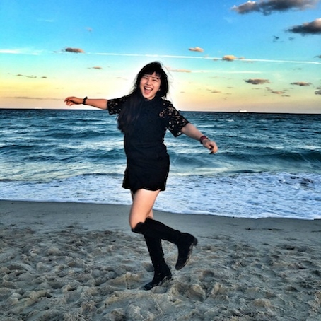 Zhen Cao in black dree and black knee high boots on the sand with ocean in bachground