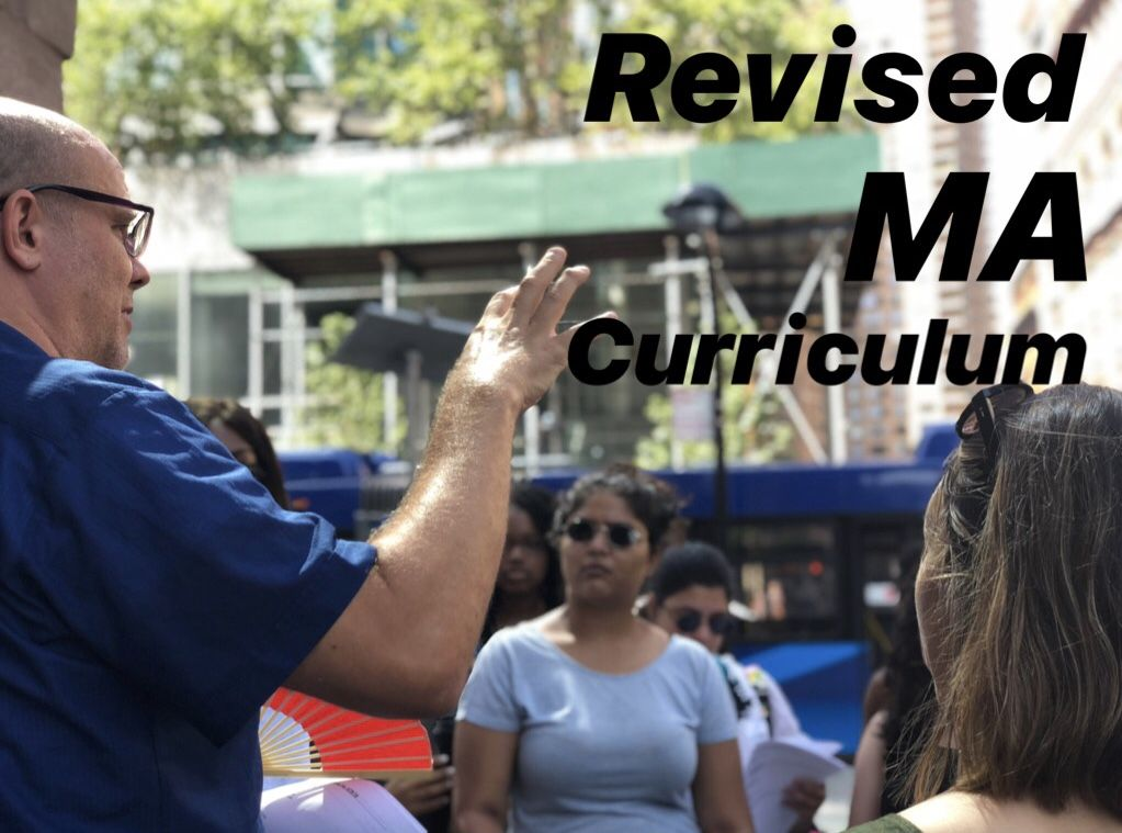 "Shoulder of man in blue shirt with hand up while students look at him. Black text reading ""revised MA curriculum"" in the upper right corner"
