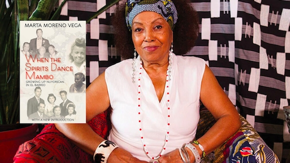 Dr. Marta Moreno Vega sits in a white shirt, bracelets and blue headscarf with hands together. Her book