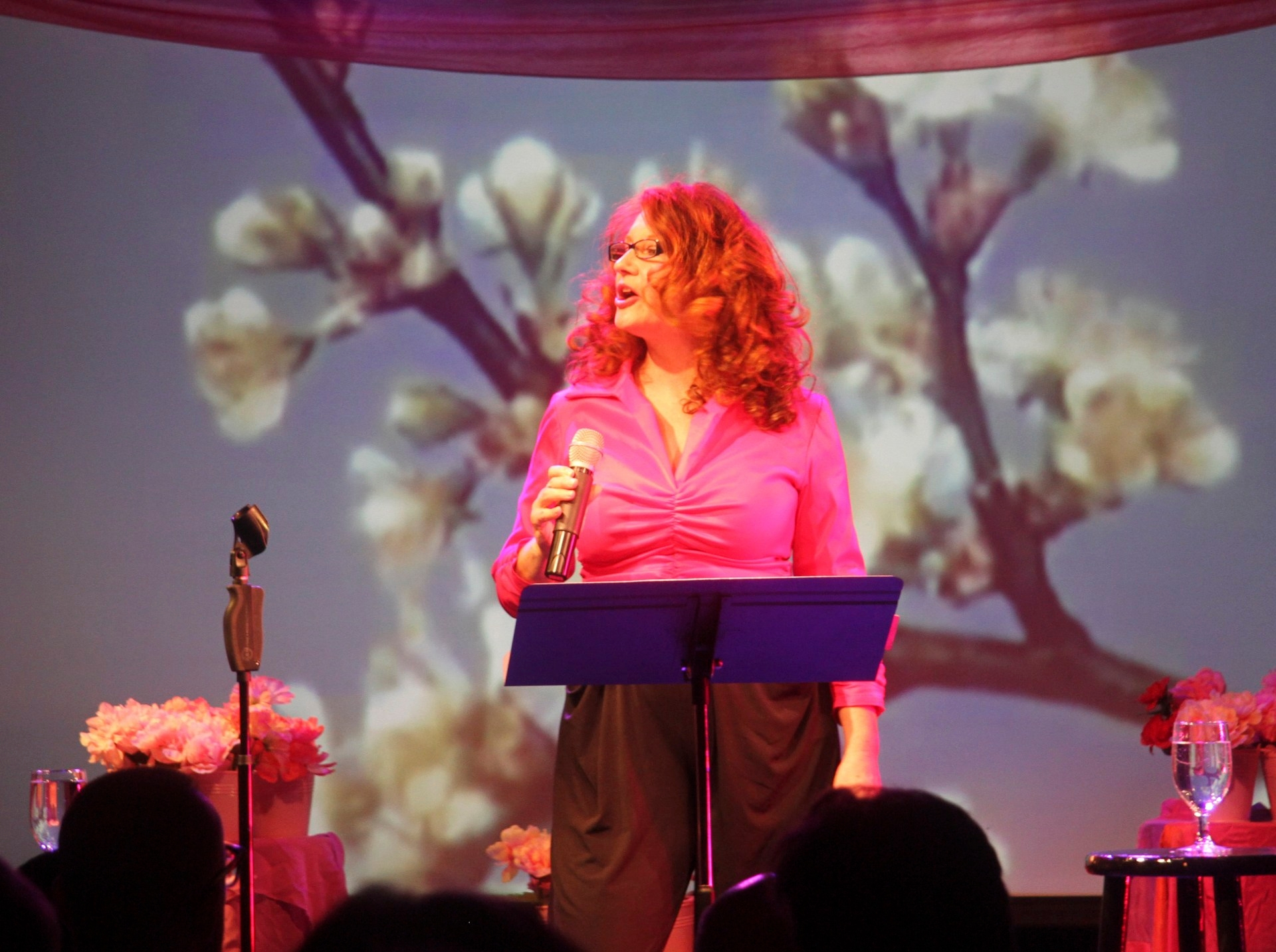 Karen Finley behind a lecturn performing in pink top in front of projection of flowers
