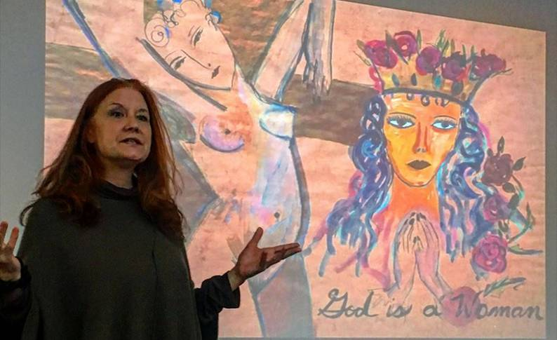 Professor Karen Finley stands in front of one of her paintings giving a lecture