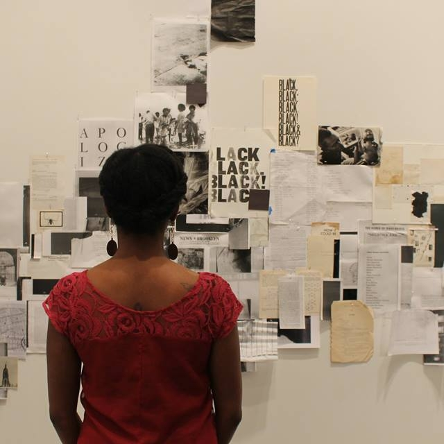 Black woman wearing red shirt, back to audience, looks at papers taped to a white wall