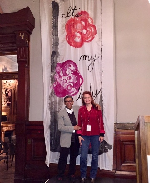 Sheril Antonio and Karen Finley in front of the hand painted banners hung in the armory.