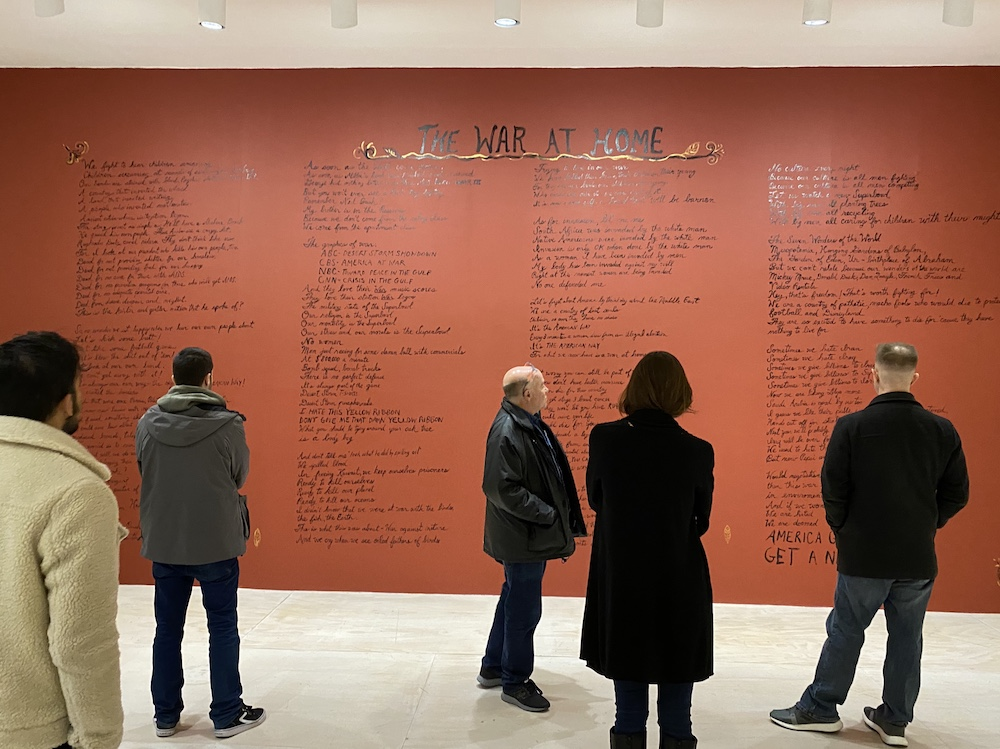 Five people stand in a gallery in front of a large red wall with black text  for The War At Home