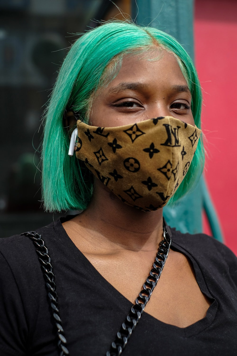 person with green hair and apple airpod wears golden Louis Vuitton printed mask