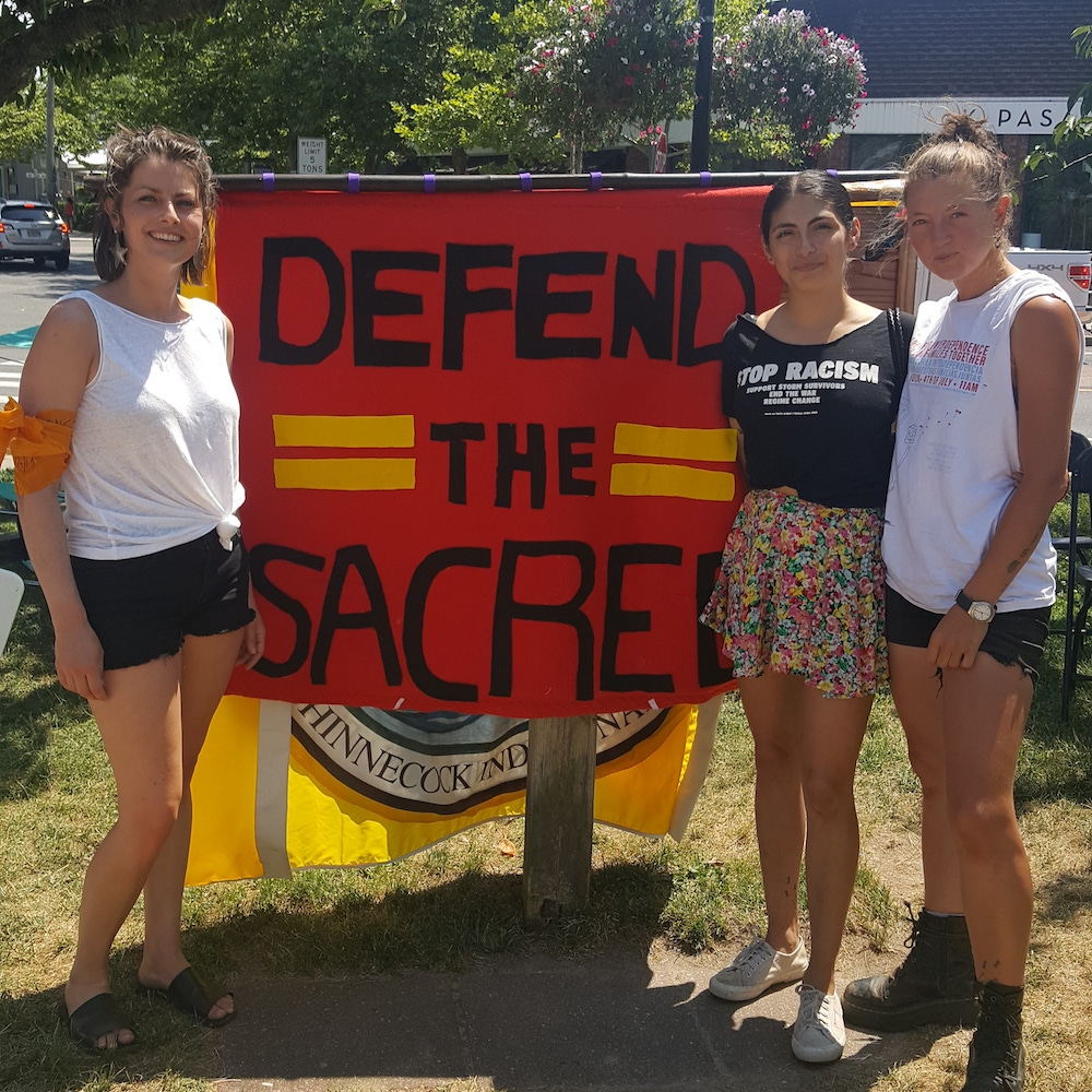 three young women stand besides red sign that reads defend the sacred