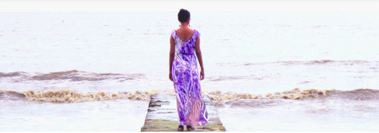 Female figure in long purple dress with hair up and wearing dangling earrings faces out towards waves