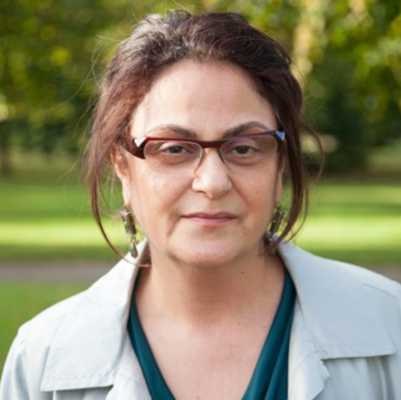 Ella Shohat headshot with green top and glasses