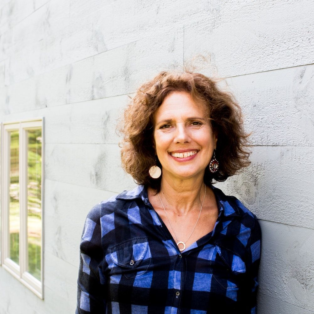 Kathy Engel in blue shirt smiling and leaning against a wall