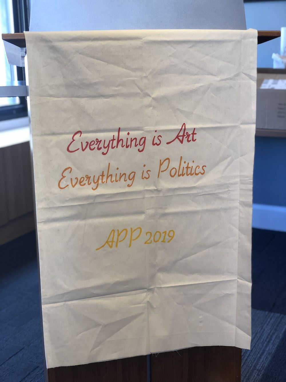 "Banner hanging on podium reading ""Everything is Arts, Everything is Politics"""