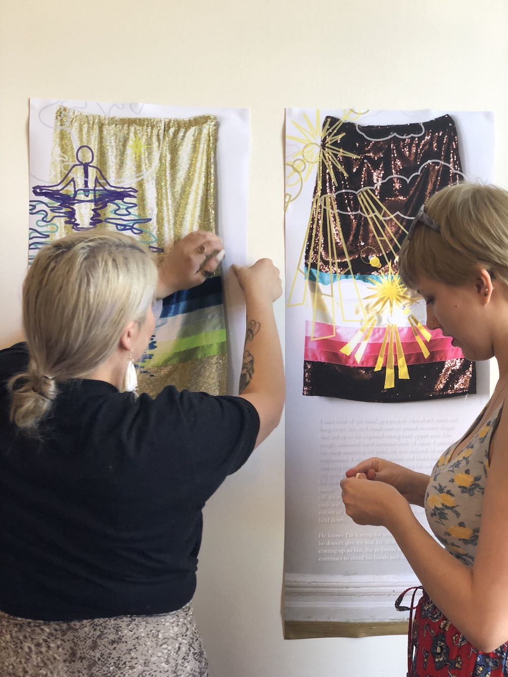 Two women hang tapestries on a wall
