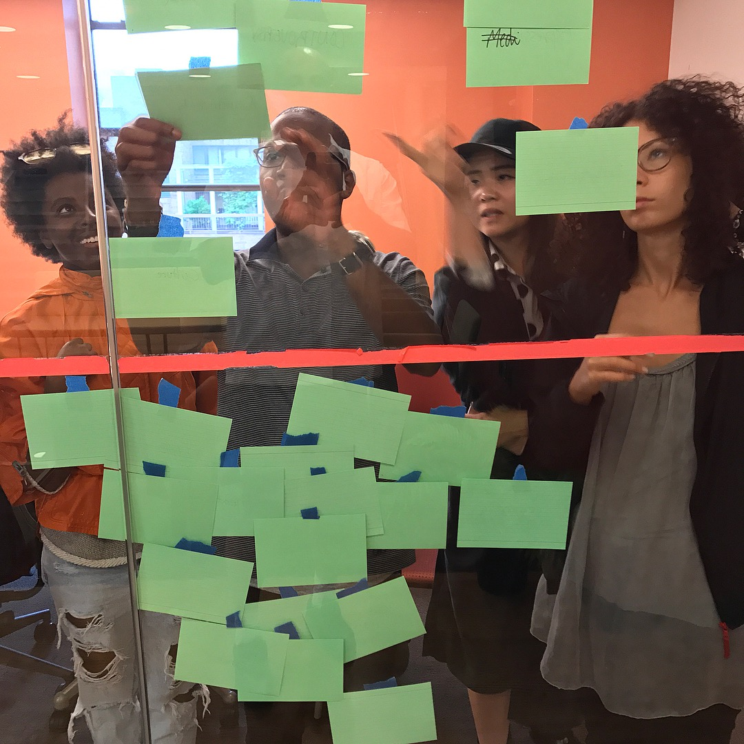 Four Arts Politics students put up green notecards on clear glass wall