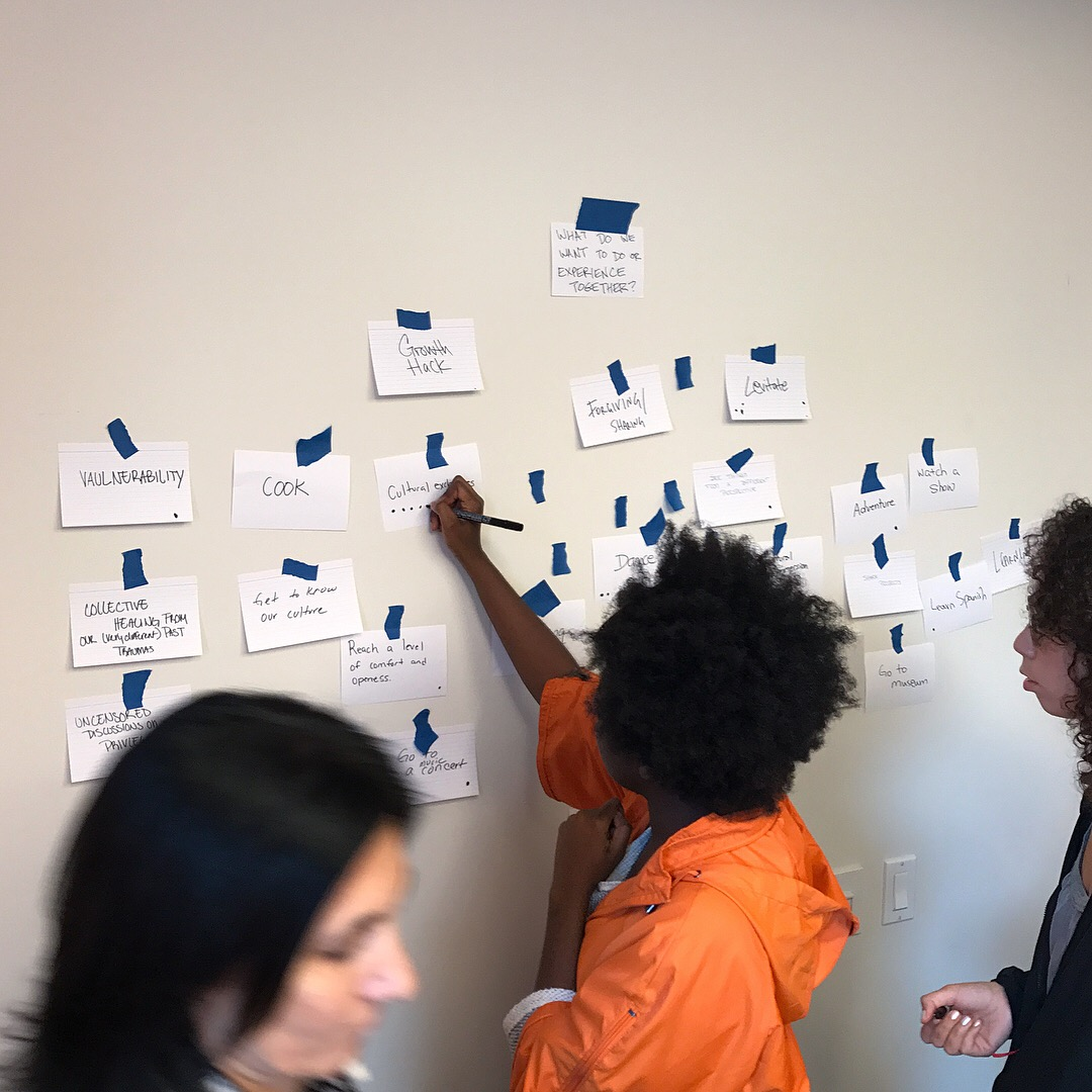Arts Politics student in orange jacket puts up white notecard on wall with words written on them