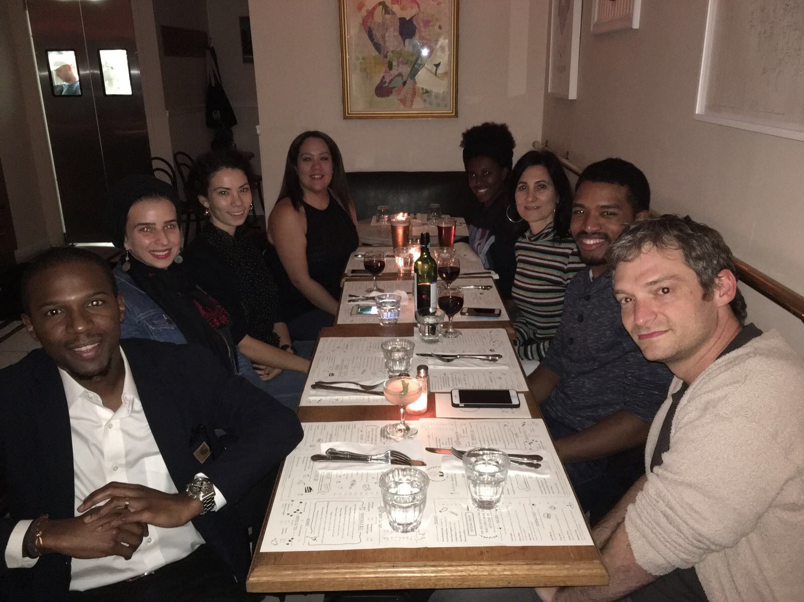 Eight people seated at a table at a restaurant for dinner