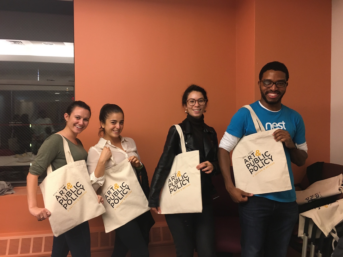 "Four people hold canvas tote bags that read ""Art & public Policy: A Decade and Beyond"""
