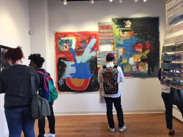 Four students examine artwork on the wall