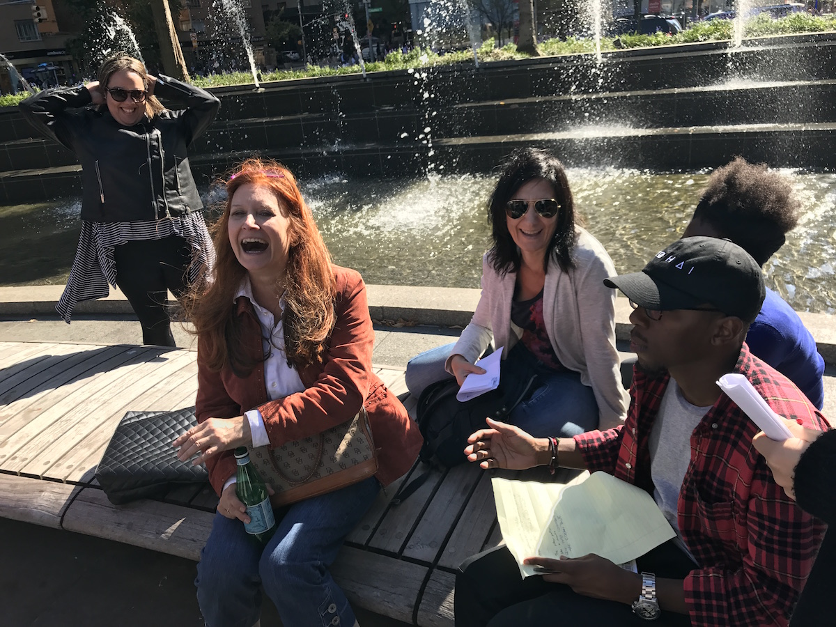 Arts Politics students and Professor Karen Finley laugh in front of foutain