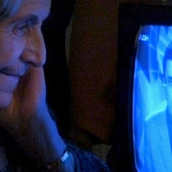 An elderly woman leaning in closely to look at a television screen, a man in a suit on the screen.