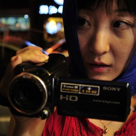 A woman wearing a blue headscarf and a red jacket pointing a video camera at another woman.