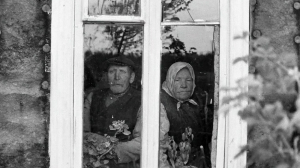 An older couple looking outward through a window.