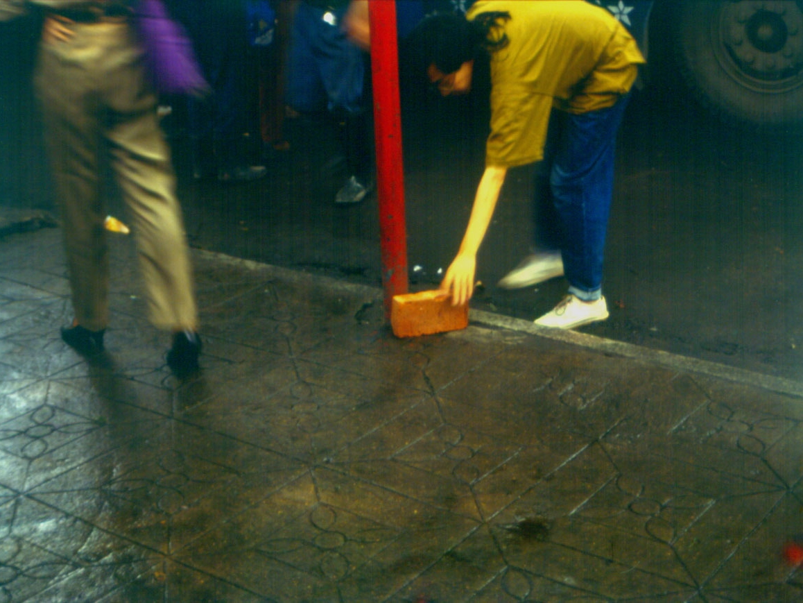 A woman bent low to the ground brushing the sidewalk with a bristle brush.