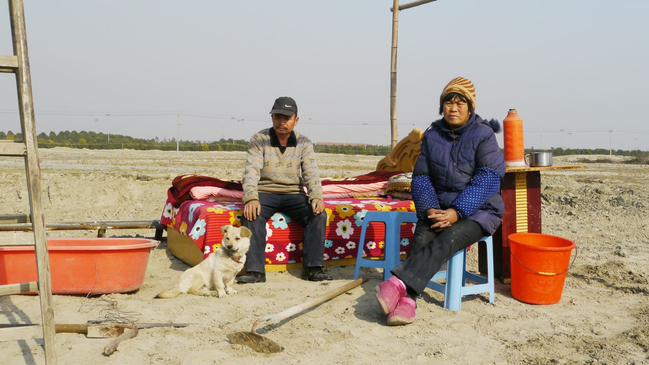A man sitting on a bed in an open plains. A dog sits at his feet. A woman is sitting on a chair to his left.