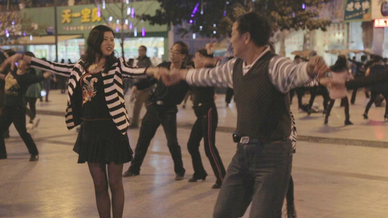 A couple dances in the street. Many dancers are visible in the background.