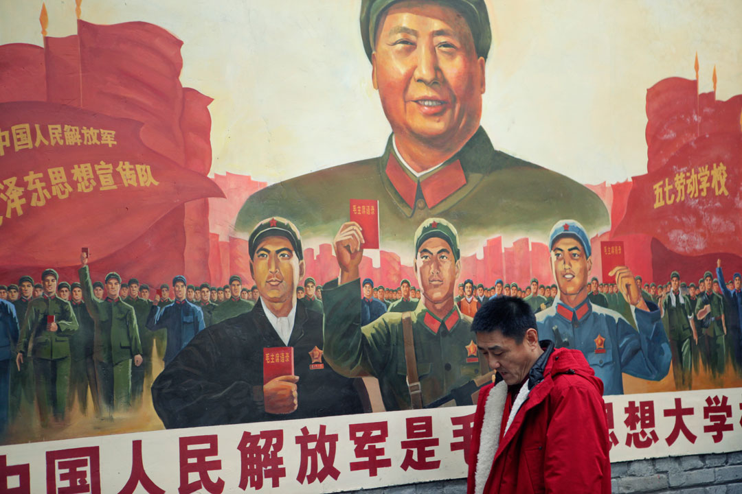 Man in a red sweatshirt walking in front of a poster of Mao Zedong