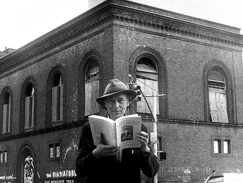 Man wearing a hat, holding a book open, in front of the building for Anthology Film Archives