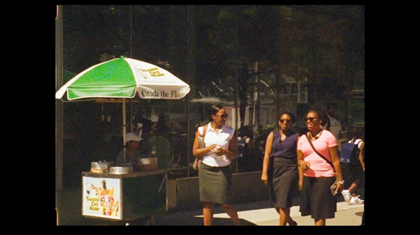 Three women wearing sunglasses, walking down the street on a sunny day, passing an ice cream vendor on the sidewalk.