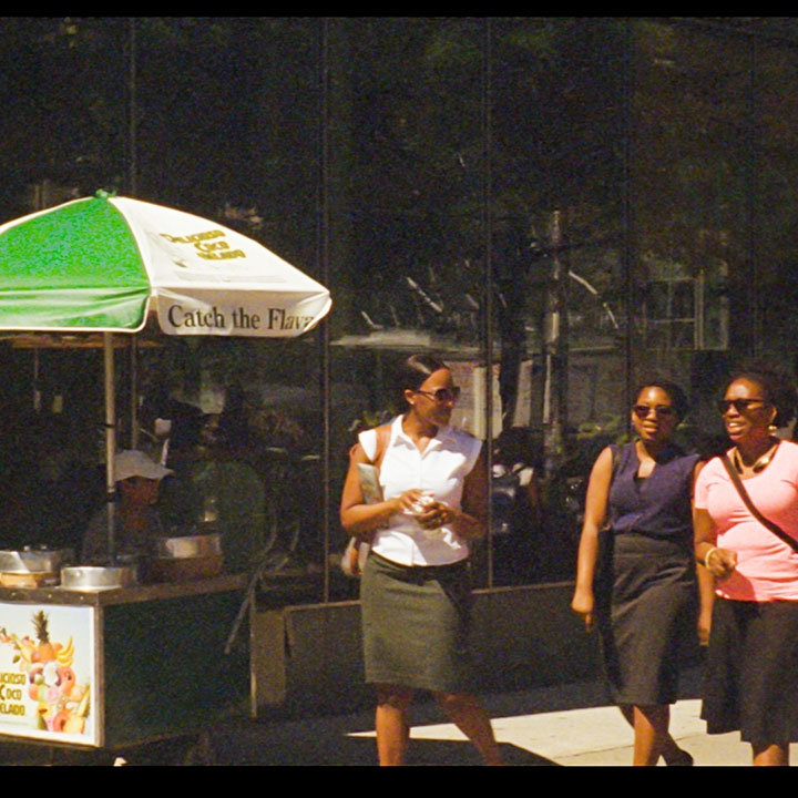 film still from the Cancer Journals Revisited, three women standing next to a foodcart on the sidewalk.