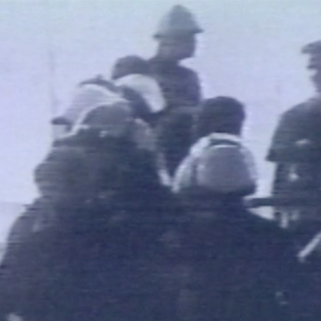 Grainy image of police in riot gear, standing in front of people wearing regular clothing.