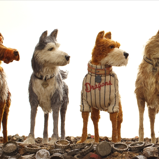 image still from the film Isle of Dogs, four claymation style dogs looking to the right side of the screen.