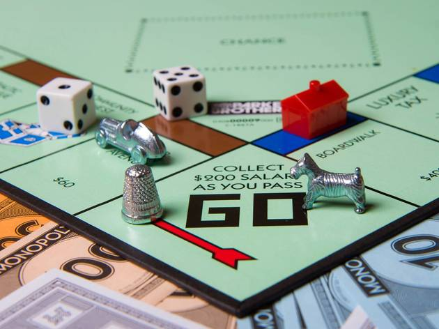 Closeup of a Monopoly board with two dice, and three players' pieces