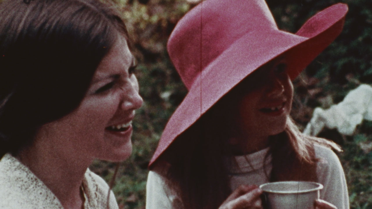 Two women laughing, one with brown hair, another wearing a red hat and drinking tea