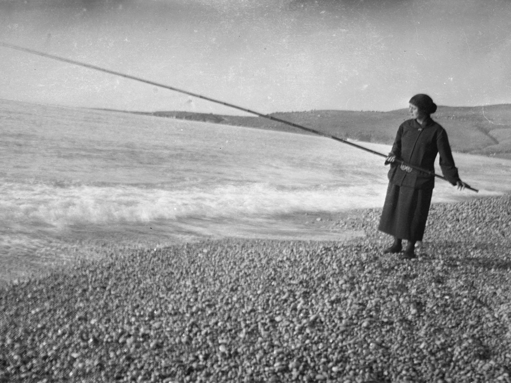 Woman on a beach holding a long pole over the water.